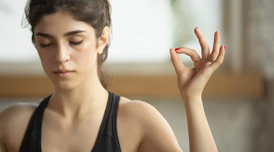 Sporty young muslim woman taking yoga lessons at home