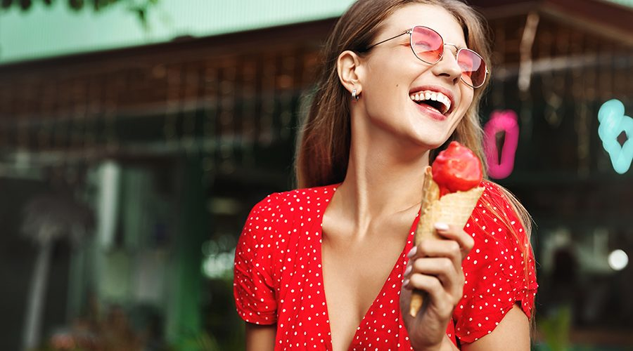 Happy young woman eating sweets on summer vacation. Female traveller licking ice cream and enjoying tropical paradise, explore city and local cuisine.